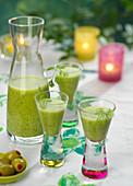 Zucchini-Gazpacho mit Erbsen serviert in Karaffe und Gläsern