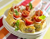 Schinkenquiche als Häppchen serviert mit Parmesan, Kirschtomate und Basilikum