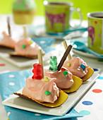 Schiffchen aus Hippen mit Schokolade, Zuckerwatte, Mikado und Gummibärchen