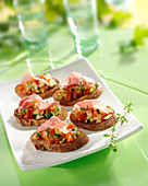 Diced vegetable and thin strips of raw ham crostinis