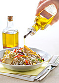Pouring olive oil on a rice, sweet corn, artichoke, pepper and red kidney bean salad