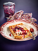 Brussels waffles with thick cream, summer fruit jam and pink icing sugar