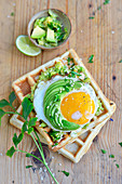 Potato waffles with guacamole, fried egg and sliced avocado