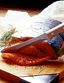 Slicing raw salmon marinated with dill