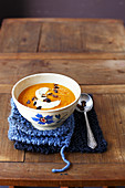 Cream of carrot and sweet potato soup with caramelized squash seeds