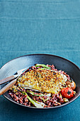 Lean fish fillet with crumble topping,red rice with tomatoes and spring onions