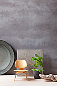 Stoneware plate and table mat with miniature wooden chair and basil plant