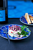 Fromage frais mixed with chopped radishes and chives timbale topped with grated red cabbage and sesame seeds