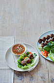 Preparing spring rolls with rice galettes,lettuce and meatballs,spicy peanut sauce