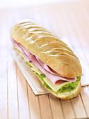 Milchweissbrot-Sandwich mit Schinken, Emmentaler, Salat und Butter