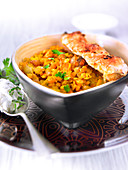 Orange lentil and raisin curry with chicken brochettes coated in coconut