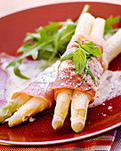 White asparagus wrapped in bacon and grilled with parmesan