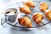 Buttercroissants auf Abkühlgitter und eine Tasse Kaffee