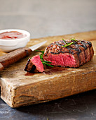 Grilled beef steak sliced on a wooden chopping board