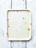 Weißes leeres und verschmutztes Ofenblech auf Holzuntergrund