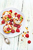 Half Nectarines Garnished With Raspberries,Almonds And Pomegranate And Whipped Cream