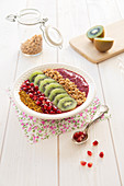 Acai-Bowl mit Granatapfel, Kiwi, Pollen und Granola