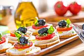 Belegte Brote mit Tomate, Mozzarella und Olive auf einem Tablett