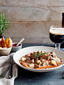 Everzwijnstoofpotje in bier met granaatappelsaus en aardappelwedges