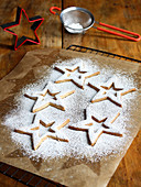 Sprinkling Icing Sugar Over Star-Shaped Christmas Cookies