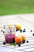 Apfel-Brombeer-Kompott im Glas auf einem Gartentisch