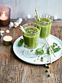 Glasses of spinach and pea juice with pepper and dried fruit crumbs