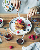 Frau isst Pancakes mit Himbeeren und Heidelbeeren
