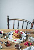 Pile of pancakes with raspberries,blueberries and maple syrup