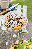 Large blueberry Financier cake on a folding chair outdoors