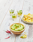 Guacamole, tortillas and glasses of Mojito for an aperitif