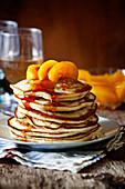 Stapel hausgemachte Pancakes mit pochierten Pfirsichen
