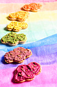 Hummus beetroot, red bean, orange lentil and spirulina, curry, carrot and pepper on cloud-shaped sesame biscuits