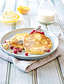 Icing sugar sprinkled on ricotta and red currant pancakes