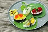 Assorted maki and sushi with horseradish, nasturtium, arugula and beet