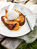 Brioche perdue with apricots in syrup and vanilla ice cream outside