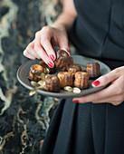 Frau hält Teller mit Canneles (Gebäck, Frankreich)