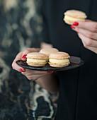 Frau hält Teller mit Macarons