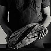 Bäcker halt Brot in den Händen (Schwarz-Weiß-Aufnahme)