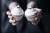 Hände halten Halloween-Muffins