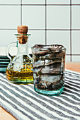 Front view of pile of salted fish in glass on towel with bottle of oil and plates behind