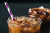 Eiskaffee mit Eiswürfeln und Strohhalm im Glas