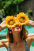 Frau hält sich zwei Sonnenblumenblüten vor die Augen