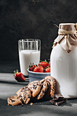 Chocolate Chip Cookies daneben Milch und Erdbeeren