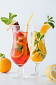 Summer fresh cocktails with strawberry, lemon and orange pieces, mint isolated on white