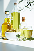 Various bottles of aromatic olive oil, jar, bowl with green olives and branches on white table