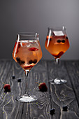 Two glasses of lemonade with ice cubes, strawberries and blueberries on grey background