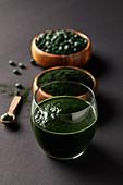 Spirulina-Smoothie dahinter Schälchen mit Algenpulver und Tabletten