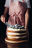 woman in pink apron cutting delicious blackberry cake on black