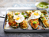 Stuffed zucchini with quinoa, corn, peppers and fried eggs