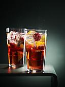 Zwei Cocktails mit Früchten und Eiswürfeln